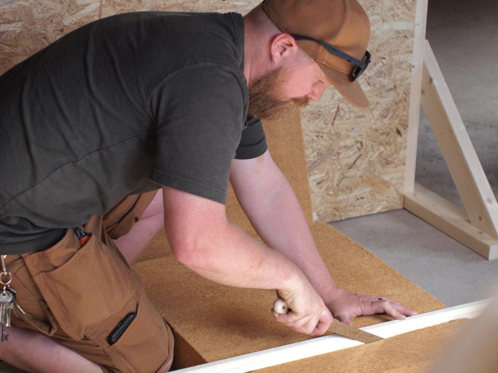 Man kapar isoleringsskivor i träfiber med isolerkniv.